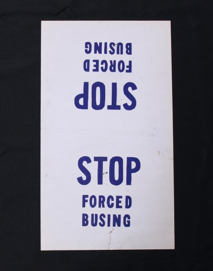 "Photograph of a white placard sign with blue text that reads: ""STOP Forced Busing."""