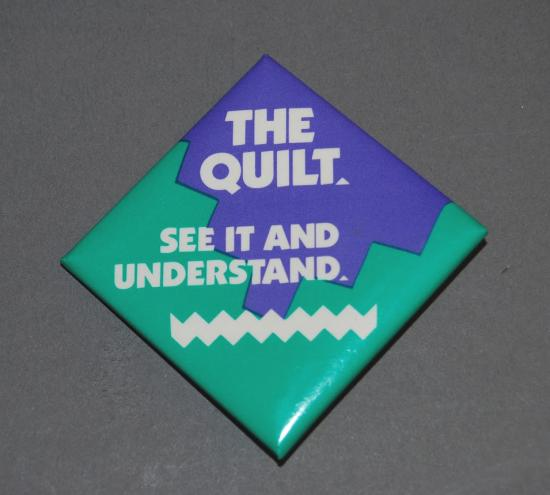 "Turquoise and purple diamond-shaped pin with text: ""The Quilt, see it and understand"""