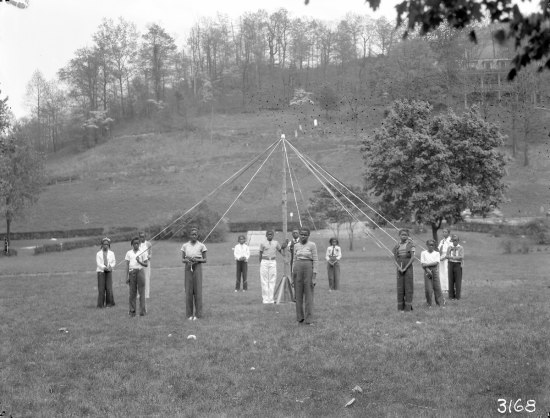 Photograph of children posing around an undecorated may-pole in everyday, non-festive clothing.