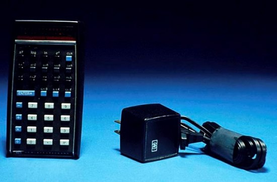 A black calculator with black, blue and white keys sits next to a wall charger, the cord wrapped up and secured