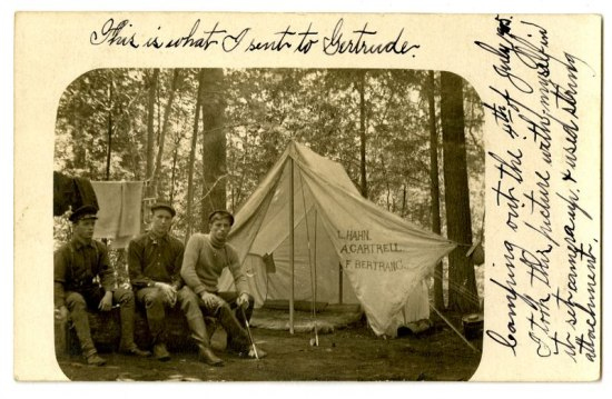 Black and white photo of three men sitting outside a tent.