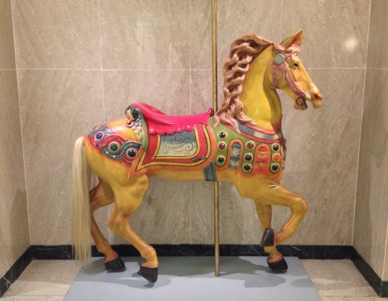 Colorful carousel horse with pink saddle and light pink mane