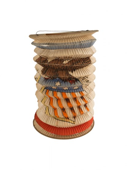 An object that appears to be made of a rolled piece of crimped paper with accordion folds that is sat upright. There is a painted design on it that appears to be an eagle with American imagery.