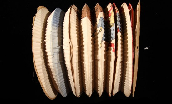 Circular, crimped paper folded like an accordion as seen from the side. There is some illustration on it that is hard to discern when it's folded.
