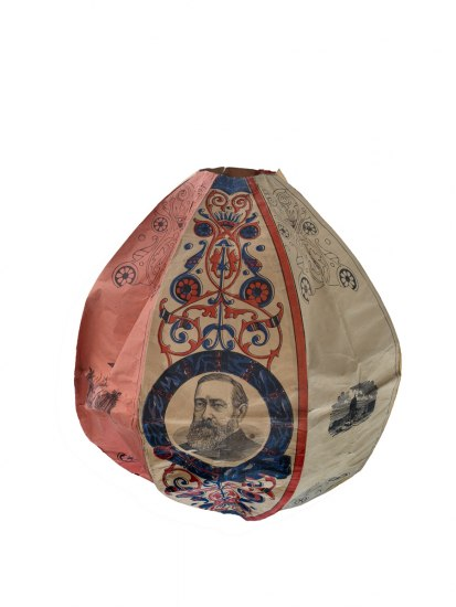 A paper object that has wiring in it to make it round like a ball. There are designs on it, such as a man's face.
