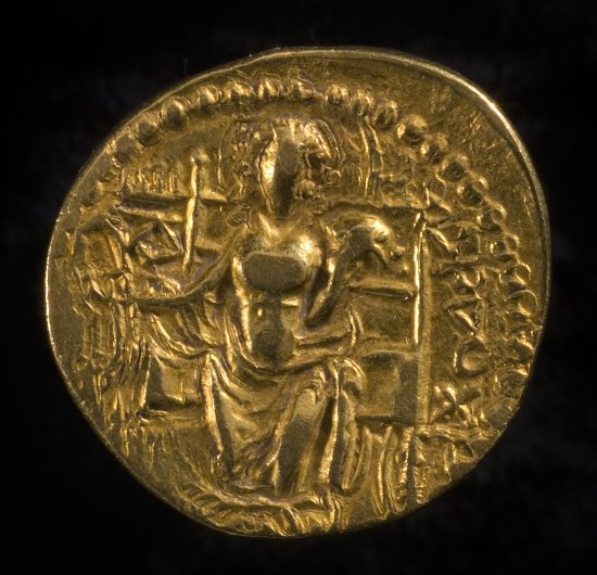 A gold coin. It is circular but the edges are not perfectly round. There is a ring design on the outside and a figure in the center that appears to be a seated woman with fabric across her lap. There are various markings and it looks like there are letters inscribed in some areas.