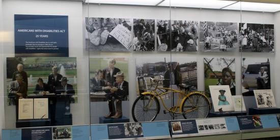 The Americans with Disabilities Act, 1990-2015 artifact wall, showing large graphics of the signing of the law by Pres. Bush, a yellow bike, and other artifacts behind glass on display in a shallow, tall case