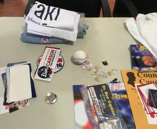 Photo of objects on table, including Ben Carson book and bumper sticker and a few pins