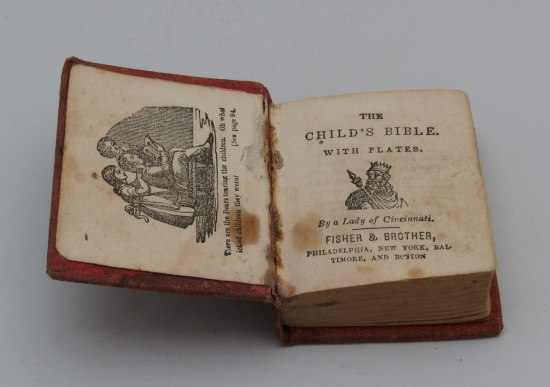 "Book open to first page. On left, a family group gathers around the Bible. On right, ""The Child's Bible with Plates"" and image of a king with crown. Black ink, white paper, faded over time and slightly stained."