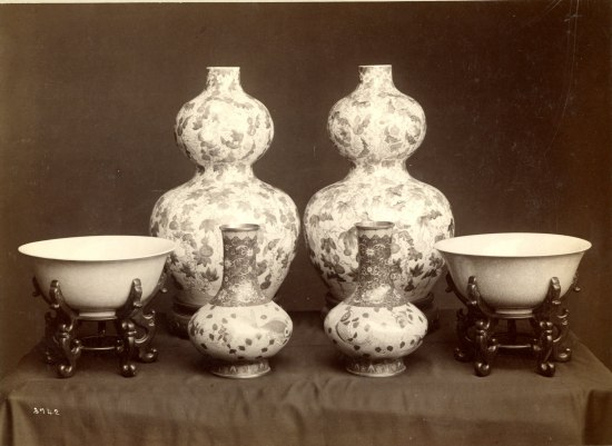 An array of white china vases. SOme have floral and intricate patterns on them. There are two bowls and four vases of varying height and design.