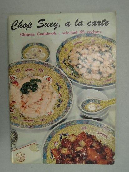 A photograph of a cook book entitled Chop Suey, a la carte. There are a number of fancy Chinese bowls positioned around with food in them, like shrimp.