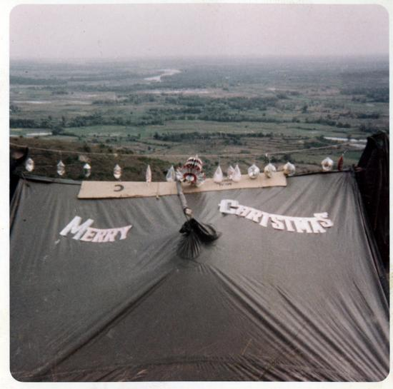 """A military tent with """"Merry Christmas"""" and decorations hanging over it"""