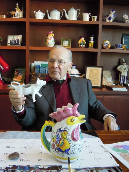 Man with glasses seated at desk with chicken-shaped water pitcher in front of him
