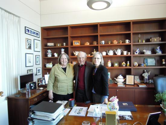 One man and two women standing in an office with wooden cabinets, desk, and white walls