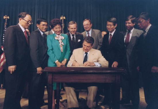 Photograph of Pres. Reagan at a desk signing document. Around him, about nine men and one woman.