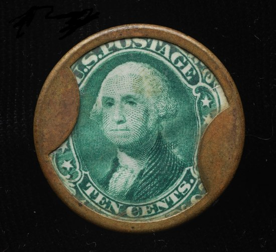 The part of the dollar bill with Washington's face in the corner is within or under a ring of metal with two metal flap-like objects.