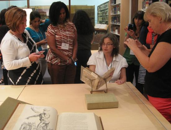 Teachers gather around a librarian with open, historic books