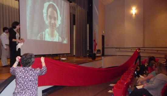 Teachers hold large strip of red fabric while video shows flagmaker from 1814