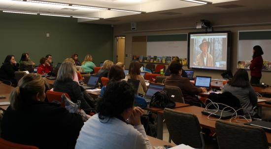Teachers in a classroom look at man in western costume on screen
