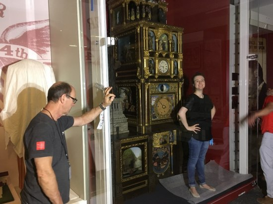 In a large, open case there is an ornate clock. A woman stands in front of it and two men hold open the doors.