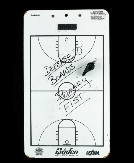 "Photo of white dry erase board with basketball court diagram on it. In marker, it is written, ""Defense 'O' Boards Primary 'FIST'"""