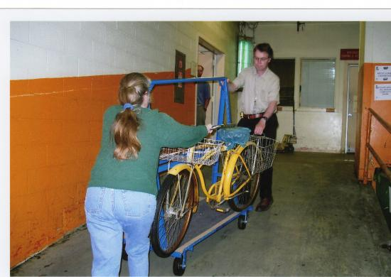 Yellow bike on blue cart being wheeled in to a hallway with yellow walls.  A woman pushes from one side, stabilizing the bike with her hand. A man pulls form the other side. The bike has baskets in front and back.
