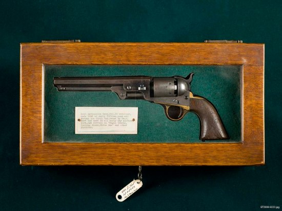 A revolver rests in green felt in a wooden box with glass inlaid in the top. There is a card laid next to it with typewriter script on it. There is a small tag attached to the key that sits in the lock.