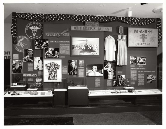 A black and white photograph of a museum display with photographs, text, costumes, and other props and objects.