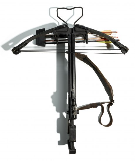 An aerial shot of a black, contemporary crossbow with several arrows stored in it