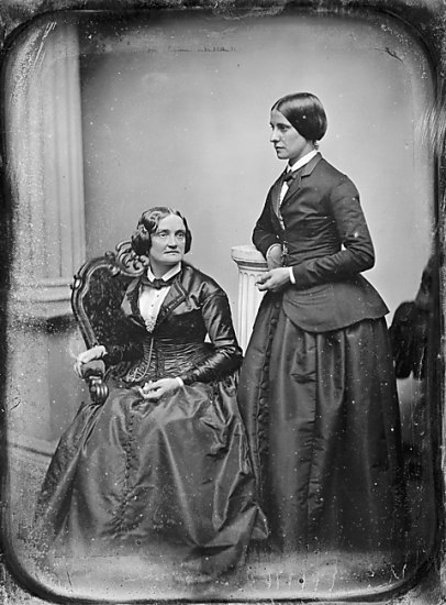 A black and white photograph of a seated woman. A younger woman stands next to her, looking in the opposite direction.