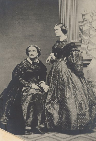 An older woman in a dark satin gown sits in this black and white photograph as a younger women in a polka dot dress looks with her to something to their right.