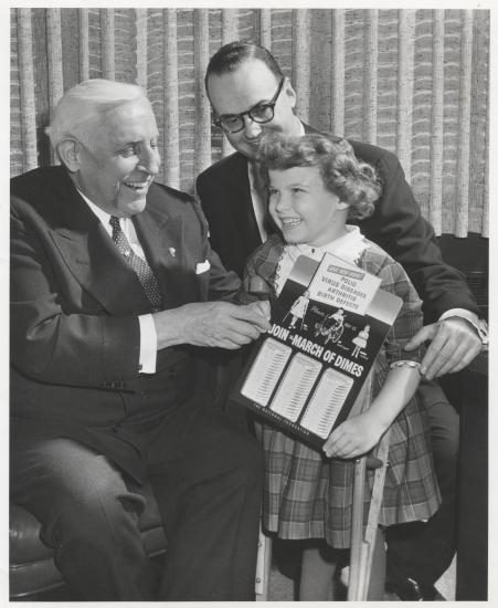 "Black and white photograph of little girl and two older white men, who are sitting. Little girl with curly hair has a huge grin and holds a sign that says ""Join mach of Dimes. Polio Virus Diseases, Arthritis, Birth Defects."" The two men are also smiling."