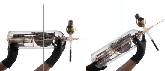 Someone wearing black gloves holds a glass instrument in two images. The instrument that looks like a glass bottle with a metal apparatus inside is held completely sideways and then at a 45 degree angle. There are red and blue lines running through each.