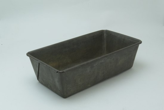 A dark metal rectangular pan. The metal looks old and it is shaped to accommodate a bread loaf.