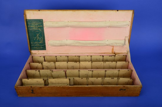 A flat wood box that is open that contains all of the paper diagrams that are mentioned in other portions of the post. They are lined up in four rows.