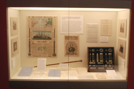 A view of a display in a wall. There are a number of objects, including letters, a cane, prints, pieces of cable, and a printed advertisement or newspaper page.