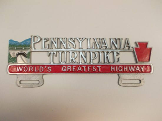 A thin piece of metal with words cut out, an illustration of a highway and bridge on the left and a red keystone on the right. There are two pieces on the bottom with thin holes.