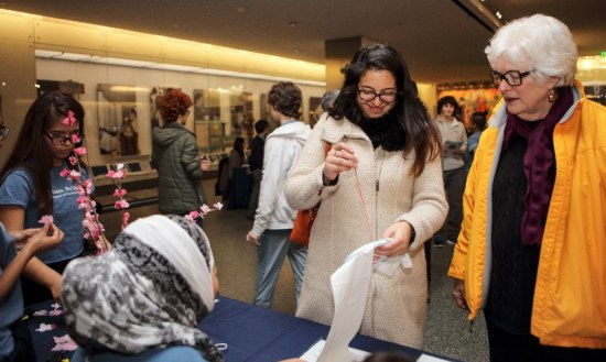 Two museum visitors visit a table with activities. One sews a red thread into a white cloth while to other watches. At the table, volunteers in blue shirts supervise the activity as well as one related to cherry blossom papers.