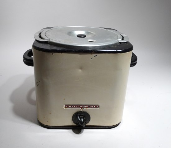"Photograph of a small kitchen appliance. It has a red label that says ""Westinghouse."" It has a lid with handle. Two black handles on the side. A single dial to control the heat, perhaps."