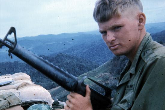 Young, blond soldier with large gun, at a high point above a mountainous landscape
