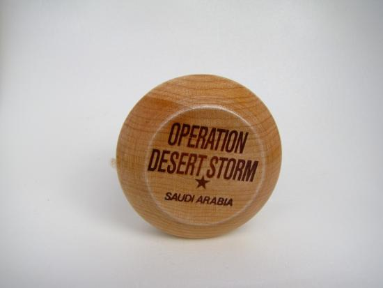 Wooden yo-yo with dark brown writing