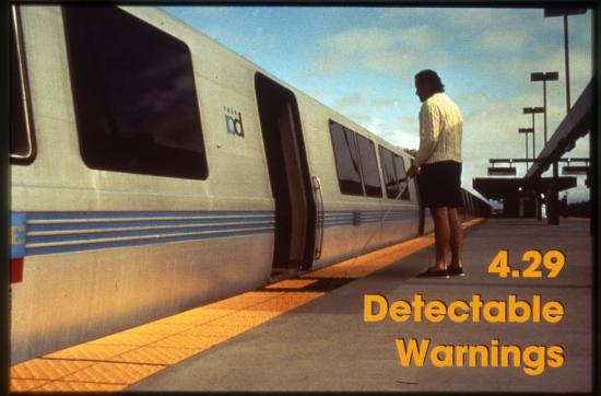 Photograph of train car and platform. Women with cane standing at car entrance. Yellow detectable warnings strip in front of her.