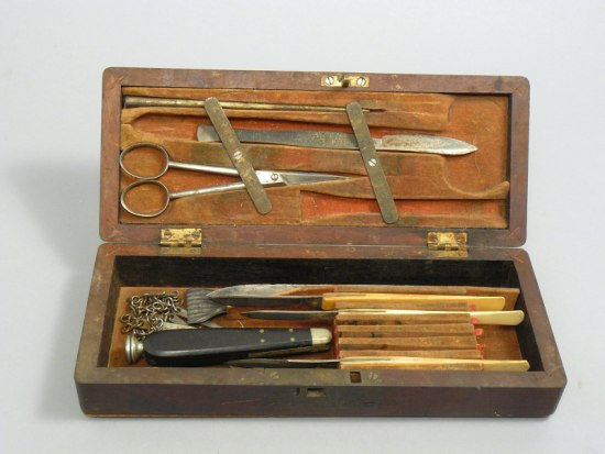 38a22a9c4 A wooden box filled with various tools that include blades and scissors