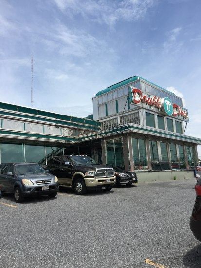 A contemporary photograph of the outside of the Double T Diner. It has a traditional chome exterior. Several cars are parked in the parking lot in front of it.