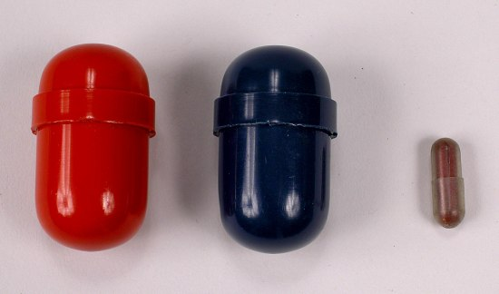 Three capsules. Two are large, one red, one blue. One is small. It is dark red.