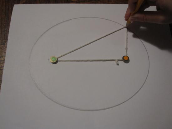 The author drawing an ellipse using pins and string