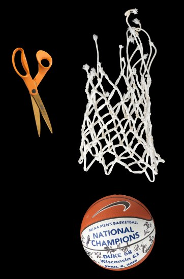 "Photo of scissors with orange handle, white basketball net, red and white basketball signed by people with ""Duke 68, Wisconsin 63, April 6, 2015"" on it."