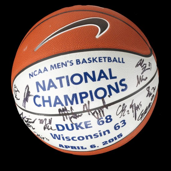 "Red and white basketball signed by people with ""Duke 68, Wisconsin 63, April 6, 2015"" on it."