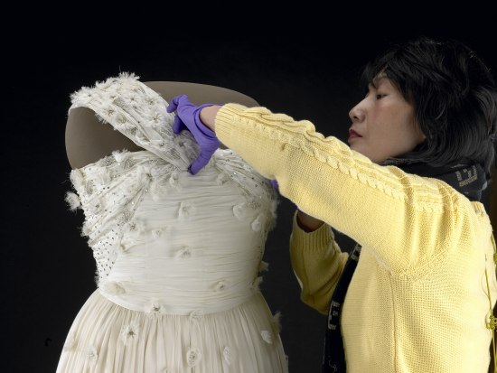 6b8cfb78 A woman wearing a yellow sweater and wearing purple gloves carefully  manipulates the fabric of a