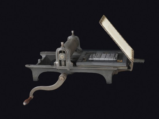 A metal object with a hand crank. There is something flat attached on one end that appears to lift and close on a block of dark metal below with white text inlaid into it in rows like the page of a book.